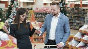 Decoraciones de compra del árbol de navidad de los pares jovenes felices en supermercado almacen de metraje de vídeo