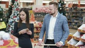 Decoraciones de compra del árbol de navidad de los pares jovenes felices en supermercado metrajes