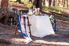 Decoraciones de la boda Zona de madera de la foto situada en bosque y adornada por la tabla, la silla, la bóveda de cristal, las  Foto de archivo