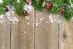 Decoraciones de la frontera de la Navidad con nieve en los tableros de madera rústicos Fotografía de archivo libre de regalías