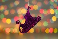 Decoraciones de la Navidad Ciérrese encima de la foto del trineo de la púrpura del Año Nuevo juguete en luz colorida Fotografía de archivo libre de regalías