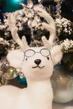 Decoraciones de la Navidad, ciervos blancos mullidos en vidrios en un fondo de la picea nevosa Imágenes de archivo libres de regalías
