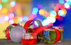Decoraciones de la Navidad con la bola, la cinta roja y la vela bajo fondo defocused Imágenes de archivo libres de regalías