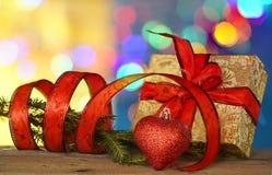 Decoraciones de la Navidad con la cinta roja, la forma del corazón y la cinta roja bajo fondo defocused Imagen de archivo libre de regalías