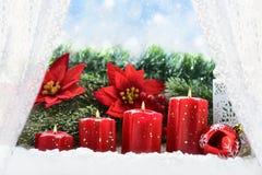 Decoraciones de la Navidad con cuatro velas del advenimiento en el sil de la ventana Imagenes de archivo
