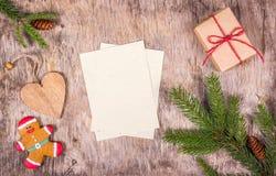 Decoraciones de la Navidad con el árbol de abeto, caja de regalo, pan de jengibre en el tablero de madera Hombre de pan de jengib Imagen de archivo