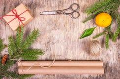 Decoraciones de la Navidad con el árbol de abeto, la caja de regalo, el papel de embalaje, la mandarina y las tijeras viejas Fotografía de archivo