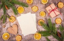 Decoraciones de la Navidad con el árbol de abeto, galletas hechas en casa, una caja de regalo y las naranjas Hoja de papel en bla Imagenes de archivo
