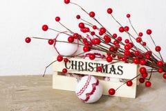 Decoraciones de la Navidad con las bayas rojas y la caja de madera en fondo del vintage Fotografía de archivo