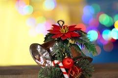 Decoraciones de la Navidad con las campanas, flores bajo fondo defocused Foto de archivo
