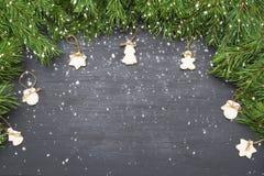 Decoraciones de la Navidad con las galletas, ramas de árbol de abeto y en fondo oscuro con el copyspace Imagen de archivo libre de regalías