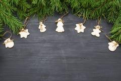 Decoraciones de la Navidad con las galletas, ramas de árbol de abeto y en fondo oscuro con el copyspace Fotografía de archivo