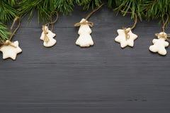 Decoraciones de la Navidad con las galletas, ramas de árbol de abeto y en fondo oscuro con el copyspace Fotos de archivo libres de regalías