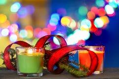 Decoraciones de la Navidad con las velas y cinta roja bajo fondo defocused Fotografía de archivo libre de regalías