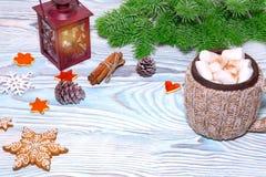 Decoraciones de la Navidad con la taza del cacao caliente, lámpara con la vela, palillos de canela, pino, rama del abeto en la ta Imagenes de archivo