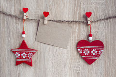 Decoraciones de la Navidad con una tarjeta en blanco que cuelga sobre la parte posterior de madera Imagen de archivo