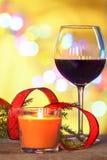 Decoraciones de la Navidad con la vela, el vino rojo y la cinta roja bajo fondo defocused Fotos de archivo