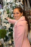 Decoraciones de la Navidad de las compras de la mujer joven en capa Fotos de archivo