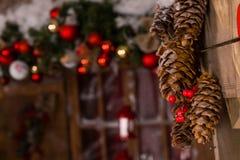 Decoraciones de la Navidad de los conos del pino que cuelgan en la pared Foto de archivo libre de regalías