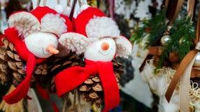 Decoraciones de la Navidad del invierno hechas de pequeños hombres rellenos con Red Hat y la bufanda en un cono del pino fotos de archivo libres de regalías
