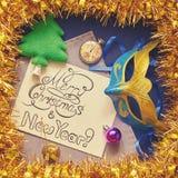 Decoraciones de la Navidad e inscripción caligráfica congratulatoria en el marco de la malla Imágenes de archivo libres de regalías