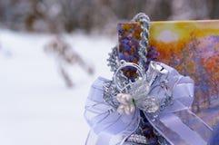 Decoraciones de la Navidad en una caja en la nieve en el bosque del invierno Imágenes de archivo libres de regalías