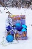 Decoraciones de la Navidad en una caja en la nieve en el bosque del invierno Fotos de archivo libres de regalías