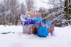 Decoraciones de la Navidad en una caja en la nieve en el bosque del invierno Fotografía de archivo libre de regalías