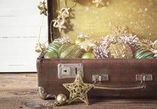 Decoraciones de la Navidad en una maleta vieja del vintage en el tablero de madera Fotos de archivo