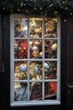 Decoraciones de la Navidad enmarcadas en ventana en venta en el mercado en Colonia Foto de archivo