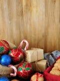 Decoraciones de la Navidad, galletas, dulces y actuales cajas envueltas en un fondo de madera Imagenes de archivo