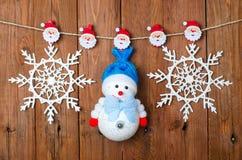 Decoraciones de la Navidad: muñeco de nieve y copos de nieve con los pernos de ropa Foto de archivo libre de regalías