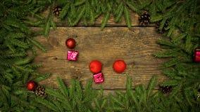 Decoraciones de la Navidad que caen en un fondo de madera con las ramas y los conos del abeto listos para su diseño Días de fiest almacen de video