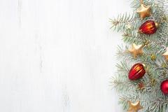 Decoraciones de la Navidad y árbol de abeto cubierto con nieve en el fondo de madera lamentable blanco Fotografía de archivo libre de regalías
