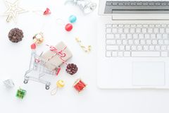 Decoraciones de la Navidad y cajas de regalo en el carro de la compra y el ordenador portátil, concepto en línea de las compras Foto de archivo libre de regalías