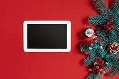 Decoraciones de la Navidad y tableta del blanco con la pantalla negra en fondo rojo caliente Tema de la Navidad y del Año Nuevo L Imagen de archivo libre de regalías