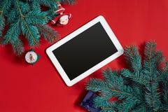 Decoraciones de la Navidad y tableta del blanco con la pantalla negra en fondo rojo caliente Tema de la Navidad y del Año Nuevo L Imagenes de archivo