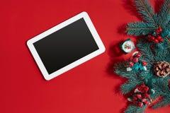 Decoraciones de la Navidad y tableta del blanco con la pantalla negra en fondo rojo caliente Tema de la Navidad y del Año Nuevo L Foto de archivo libre de regalías