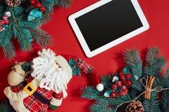 Decoraciones de la Navidad y tableta del blanco con la pantalla negra en fondo rojo caliente Tema de la Navidad y del Año Nuevo L Fotografía de archivo