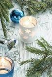 Decoraciones de las velas, de la Navidad y ramas spruce en un t de madera Fotografía de archivo