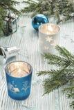 Decoraciones de las velas, de la Navidad y ramas spruce en una tabla de madera Fotos de archivo