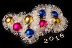 Decoraciones de los días de fiesta del ` s de la Navidad y del Año Nuevo Bolas multicoloras y guirnalda de la Navidad aisladas en Imagen de archivo