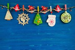 Decoraciones de madera y del fieltro de la Navidad y luces de la Navidad en una cuerda en el fondo de madera azul Foto de archivo libre de regalías