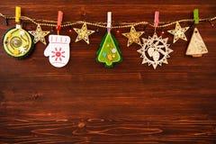Decoraciones de madera y del fieltro de la Navidad y luces de la Navidad en una cuerda en el fondo de madera marrón Foto de archivo libre de regalías