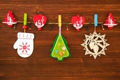 Decoraciones de madera y del fieltro de la Navidad y luces de la Navidad en una cuerda en el fondo de madera marrón Imagenes de archivo