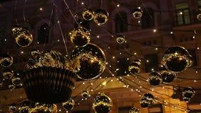 Decoraciones de oro brillantes que cuelgan al aire libre, chispeando para crear humor festivo almacen de video