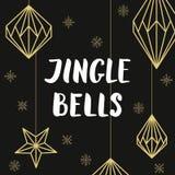 Decoraciones de oro de la Navidad y Jingle Bell que pone letras handdrawn Fotografía de archivo libre de regalías