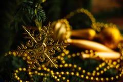 Decoraciones de oro de la Navidad en una caja, primer, vertical Foto de archivo libre de regalías
