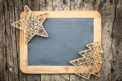 Decoraciones del árbol de navidad del oro en la pizarra de madera del vintage Fotos de archivo