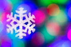 Decoraciones del árbol de navidad - el copo de nieve contra la guirnalda borrosa enciende el fondo Fotografía de archivo libre de regalías